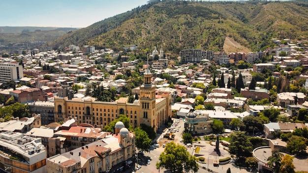Vista aérea do drone de tbilisi, geórgia. antigos edifícios residenciais ao redor com muito verde