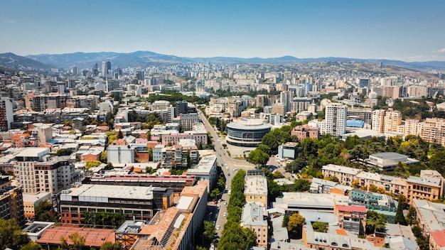 Vista aérea do drone de tbilisi, geórgia. vários edifícios, muito verde, estrada com trânsito