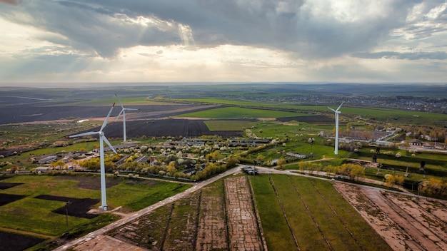 Vista aérea do drone de turbinas eólicas na moldávia. campos amplos ao redor, vila