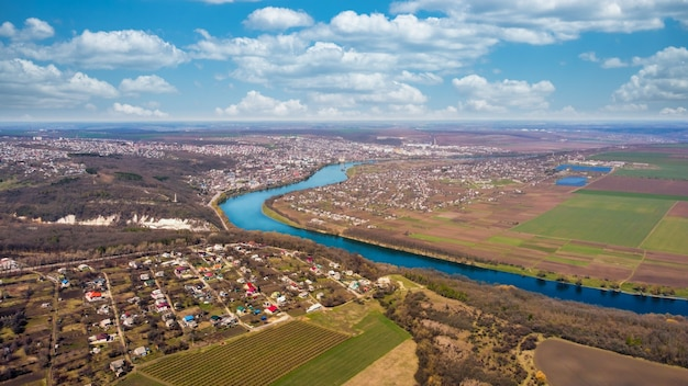 Vista aérea do drone de uma cidade na moldávia. rio, edifícios residenciais antigos, campos ao redor, árvores nuas