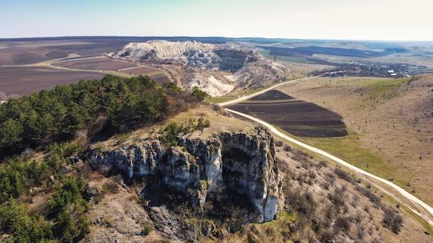 Vista aérea do drone de uma pedreira de calcário na moldávia. penhasco rochoso em primeiro plano, campos ao redor