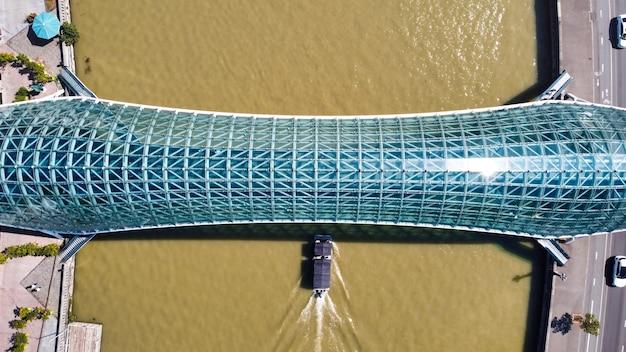 Vista aérea do drone de uma ponte moderna em tbilisi, geórgia. rio kura com barco em movimento, vista vertical