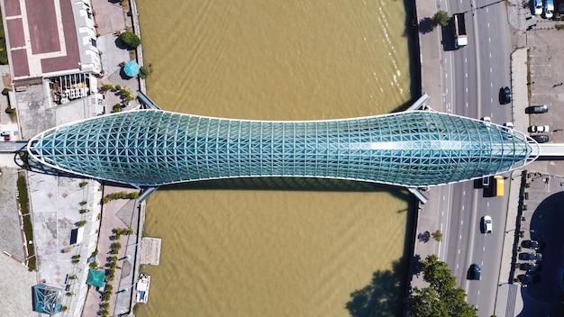 Vista aérea do drone de uma ponte moderna em tbilisi, geórgia. rio kura, trânsito, vista vertical