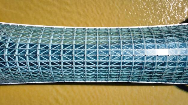 Vista aérea do drone de uma ponte moderna em tbilisi, geórgia. rio kura, vista vertical