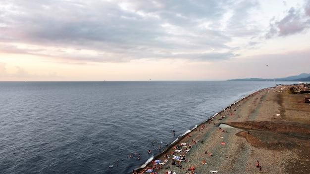 Vista aérea do drone de uma praia em batumi, geórgia ao pôr do sol no mar negro nadando e descansando as pessoas