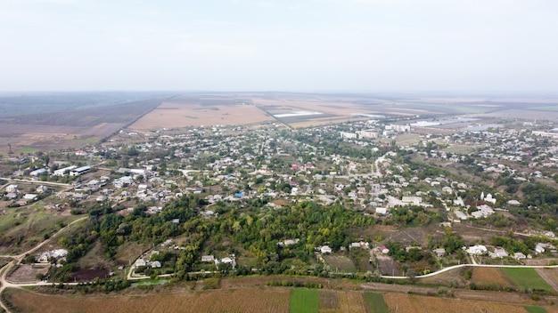 Vista aérea do drone de uma vila na moldávia, vários edifícios e árvores, névoa no ar