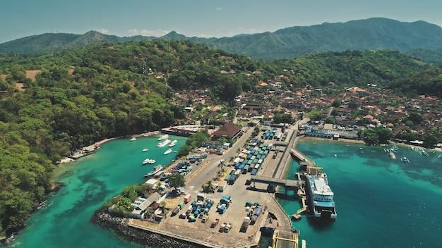 Vista aérea do drone de volta sobre o vilarejo do telhado vermelho da cordilheira verde e o belo porto oceânico