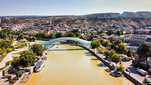 Vista aérea do drone do rio tbilisi, georgia kura, com uma ponte moderna sobre ele repleta de vegetação