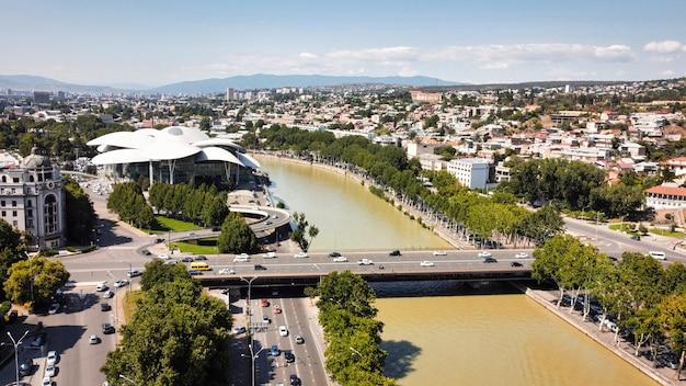 Vista aérea do drone do rio tbilisi, georgia kura, com uma ponte sobre ele repleta de vegetação