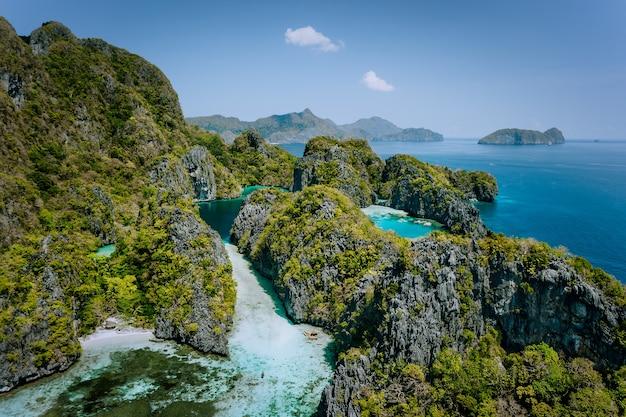 Vista aérea do drone turquesa de grandes e pequenas lagoas cercadas por rochas íngremes, reserva nacional marinha em el nido, palawan.