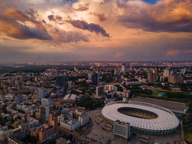 Vista aérea do estádio de futebol da cidade com o pôr do sol e belas nuvens como pano de fundo