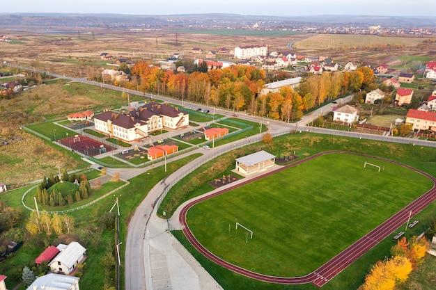 Vista aérea do estádio esportivo com pistas de corrida vermelhas e campo de futebol de grama verde.