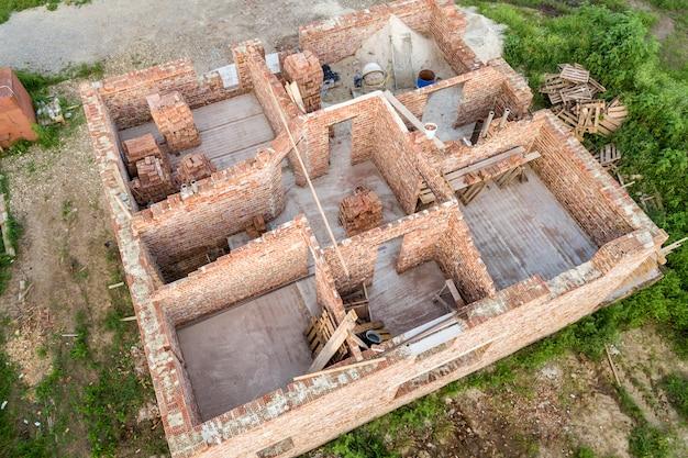 Vista aérea do estaleiro para futura casa, piso do porão de tijolo e pilhas de tijolos para construção.