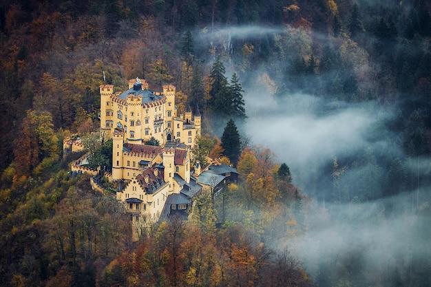 Vista aérea do famoso castelo da baviera hohenschwangau com uma bela neblina na floresta na temporada de outono
