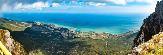 Vista aérea do fascinante panorama pitoresco de colinas, montanhas e uma vila costeira