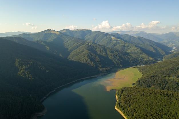 Vista aérea do grande lago com água azul clara entre colinas de alta montanha cobertas por densa floresta perene.