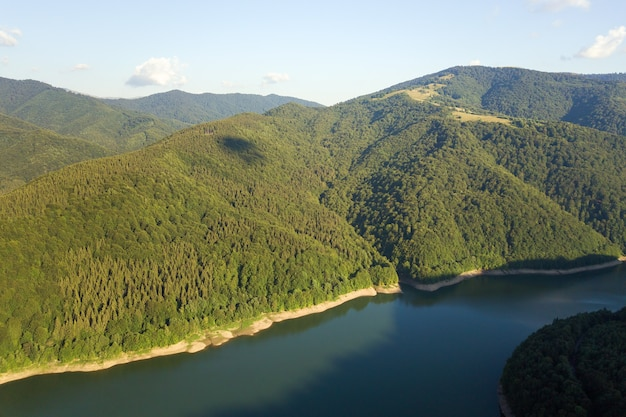 Vista aérea do grande lago com águas azuis claras entre colinas de alta montanha cobertas por densa floresta perene.