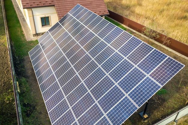 Vista aérea do grande painel solar azul instalado na estrutura do solo perto de casa particular.