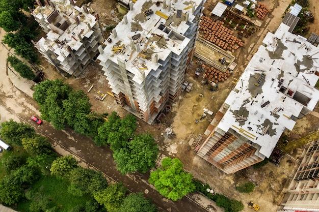 Vista aérea do guindaste de elevação de torre e estrutura de concreto de edifícios residenciais de apartamentos altos em construção em uma cidade.