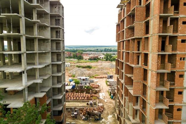 Vista aérea do guindaste de levantamento da torre e quadro concreto de prédios residenciais de apartamentos altos em construção em uma cidade. desenvolvimento urbano e conceito de crescimento imobiliário.