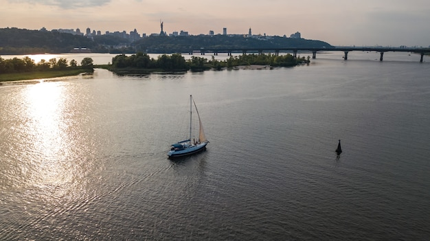 Vista aérea do horizonte da cidade de kiev no pôr do sol, iate navegando no rio dnieper de cima, kiev, ucrânia