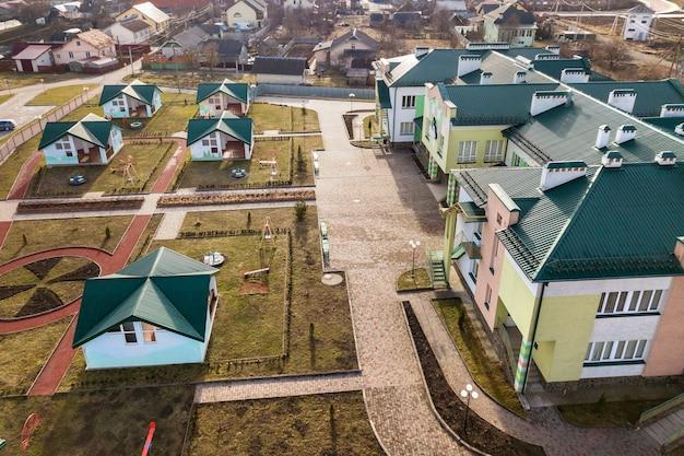 Vista aérea do jardim de infância ou complexo escolar moderno, telhados decorados e playground colorido no quintal ensolarado.