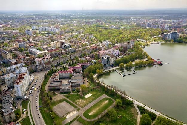 Vista aérea do lago da cidade entre árvores verdes e edifícios da cidade na zona do parque de recreação. fotografia de zangão.
