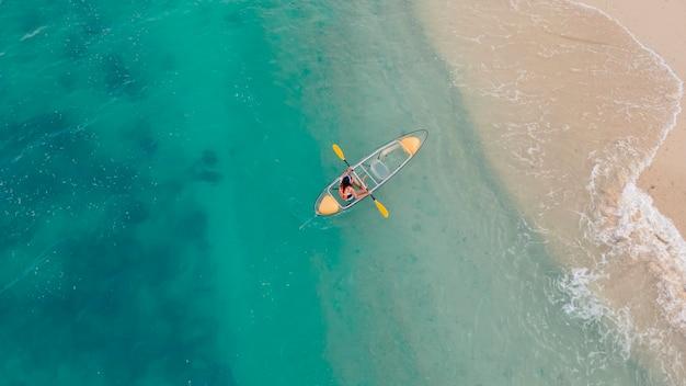 Vista aérea do mar azul com caiaque flutuante transparente indo para a praia de areia, pessoa com colete salva-vidas no barco