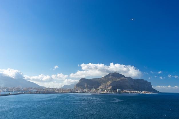 Vista aérea do mar de palermo com montanhas e nuvens no fundo, capital da sicília.