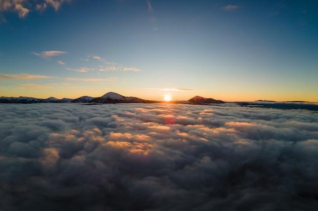 Vista aérea do nascer do sol vibrante sobre a névoa branca densa com distantes montanhas escuras dos cárpatos no horizonte.