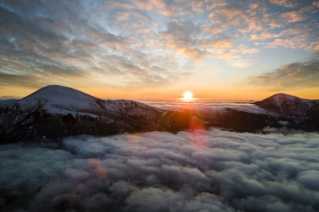 Vista aérea do nascer do sol vibrante sobre nuvens densas brancas com montanhas escuras distantes no horizonte.