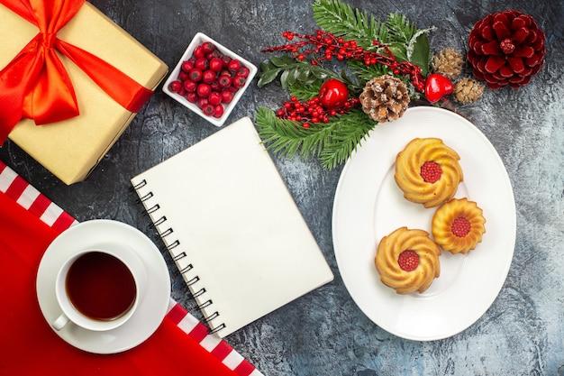 Vista aérea do notebook, uma xícara de chá preto em uma toalha vermelha e biscoitos em um prato branco. acessórios de ano novo. presente com fita vermelha na superfície escura