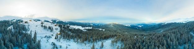 Vista aérea do panorama deslumbrante de inverno das encostas nevadas e colinas entre as exuberantes nuvens brancas.