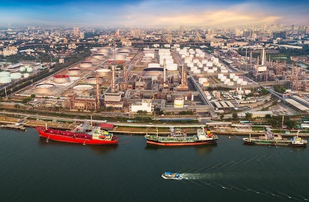 Vista aérea do porto de embarque e refinador de petróleo na cidade à beira do rio com drone