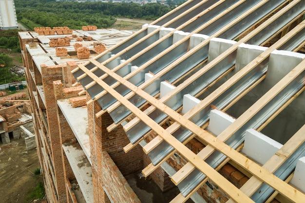 Vista aérea do prédio inacabado de tijolos com estrutura de telhado de madeira em construção.