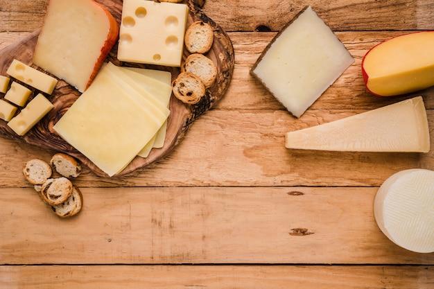 Vista aérea do queijo fresco vívido arranjado sobre a superfície de madeira
