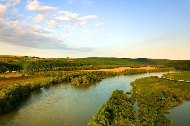 Vista aérea do rio brilhante fluindo através de prados verdes na primavera.