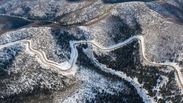 Vista aérea do rio e das florestas de taiga e da estrada no inverno primavera paisagem abstrata da natureza do norte com drone