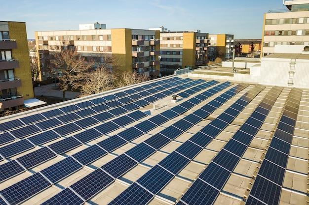 Vista aérea do sistema solar azul brilhante dos painéis voltaicos da foto no telhado comercial produzindo energia limpa renovável.