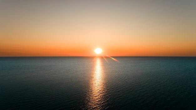 Vista aérea do sol nascendo sobre o mar.