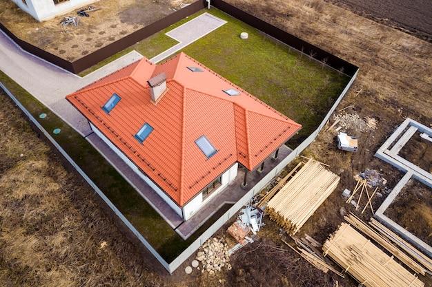 Vista aérea do telhado da nova casa com janelas de sótão e canteiro de obras, fundação da futura casa, pilhas de tijolos e toras de madeira para construção.