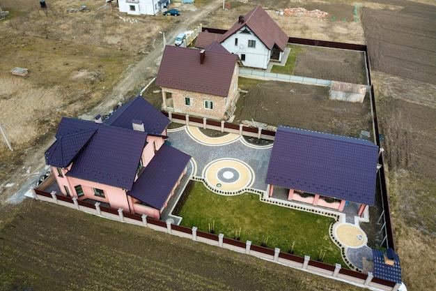 Vista aérea do telhado de telhas da casa no fundo do gramado verde e colorido pátio pavimentado com padrão geométrico abstrato.