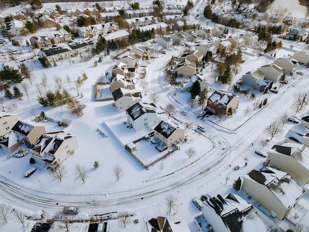 Vista aérea do topo da paisagem das casas residenciais da cidade de inverno com neve em estradas e casas cobertas.