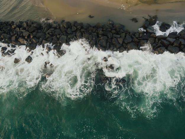 Vista aérea do topo das ondas do mar batendo nas pedras na praia na itália. água do mar ondulada e limpa.