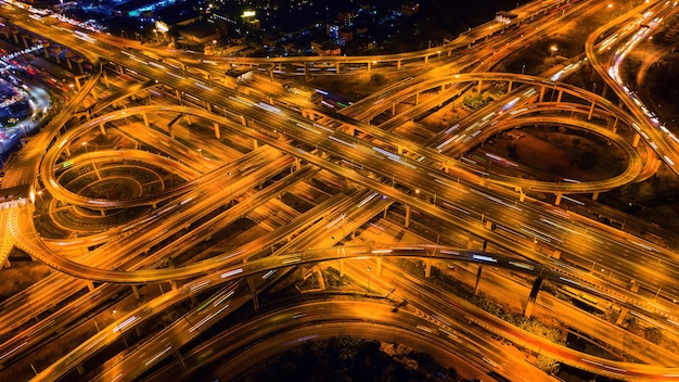 Vista aérea do tráfego no cruzamento da rodovia maciça à noite.