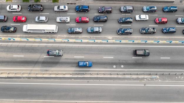 Vista aérea do tráfego rodoviário de automóveis de muitos carros na rodovia acima do transporte da cidade