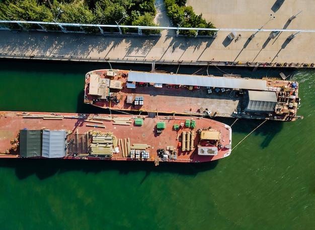 Vista aérea do transporte de carga flutuante por materiais de construção transportados, tubos de construção e estruturas metálicas em barcaças