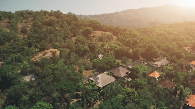 Vista aérea do vôo do drone sobre o pôr do sol na cordilheira verde da vila do telhado vermelho.
