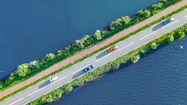 Vista aérea do zangão da estrada de auto-estrada e ciclovia na represa polder, tráfego de carros de cima, holanda do norte, holanda