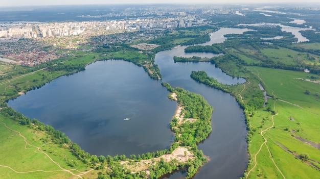 Vista aérea do zangão da paisagem urbana de kiev, rio dnieper e dniester, ilha verde de cima, horizonte da cidade de kiev e parques naturais na primavera, ucrânia